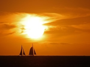 Photo of a sunset in Hawaii with sailboats